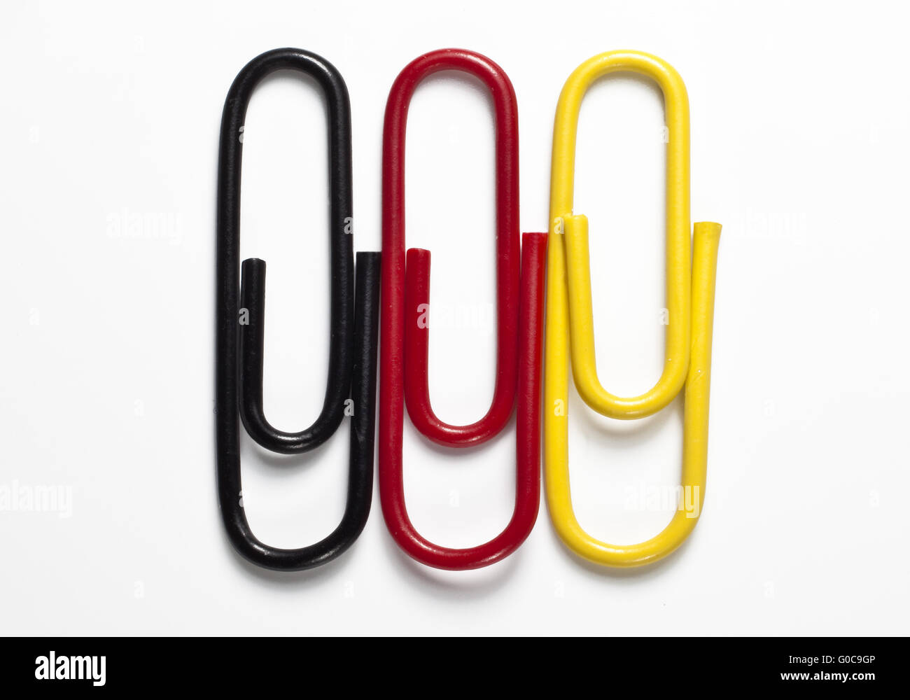 Black, red and yellow paper clips, Germany - Stock Image