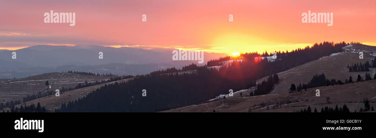 Panoramic image of rising sun in Carpathian mountains - Stock Image