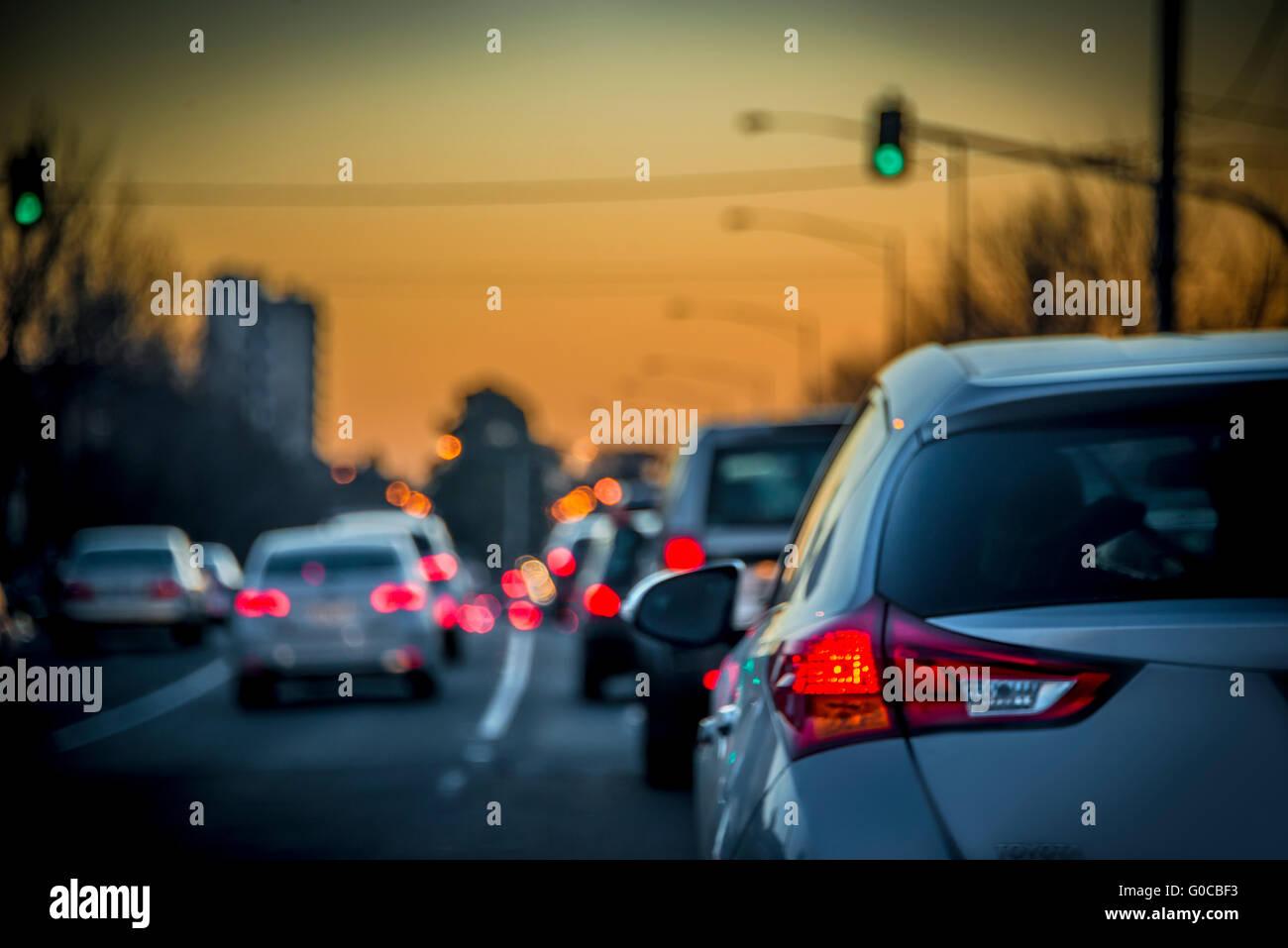 Car tail lights sitting in traffic building up on Melbourne freeway peak hour at dusk, Melbourne, Australia - Stock Image