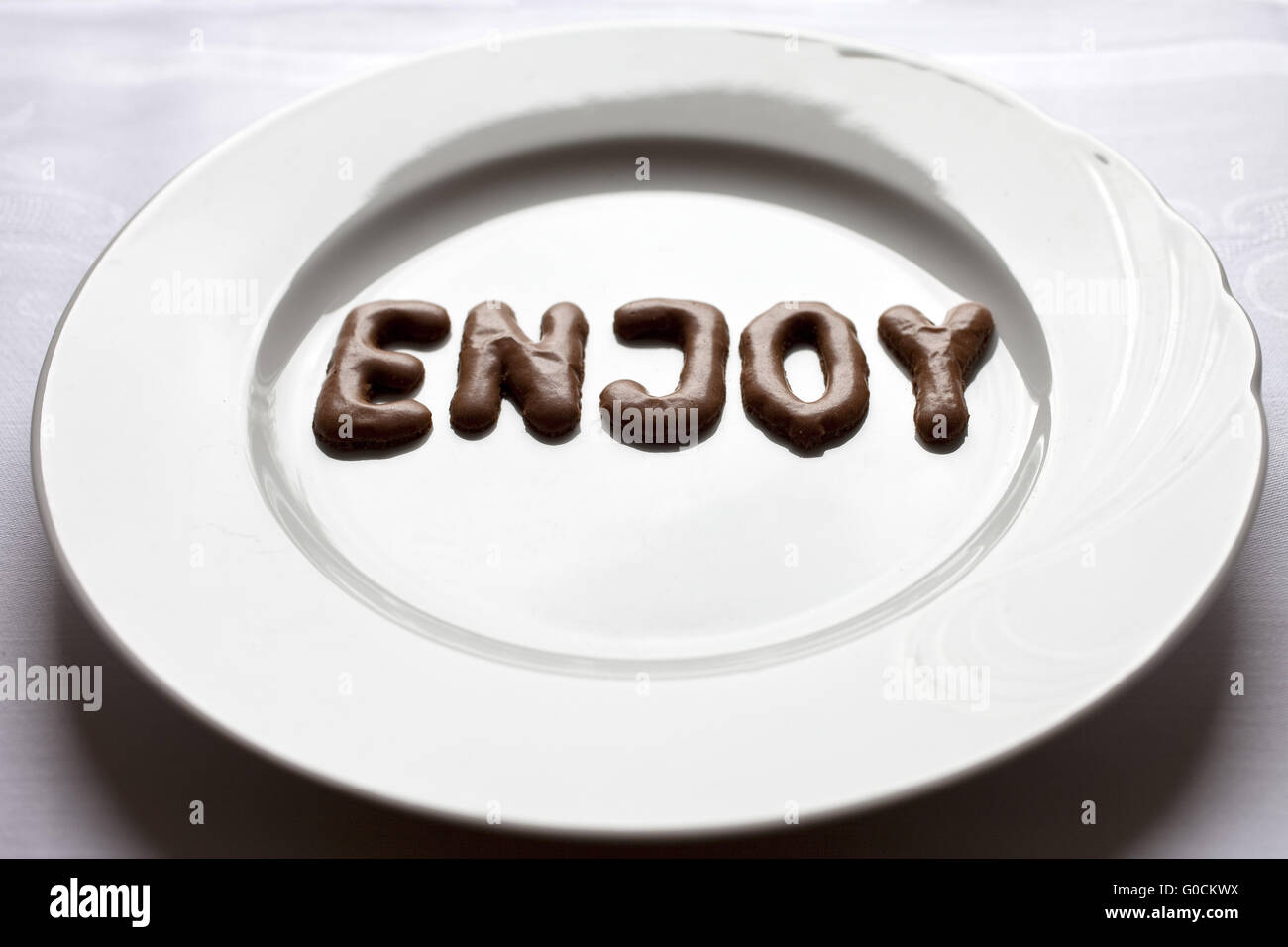 Letters forming the word enjoy on a plate - Stock Image
