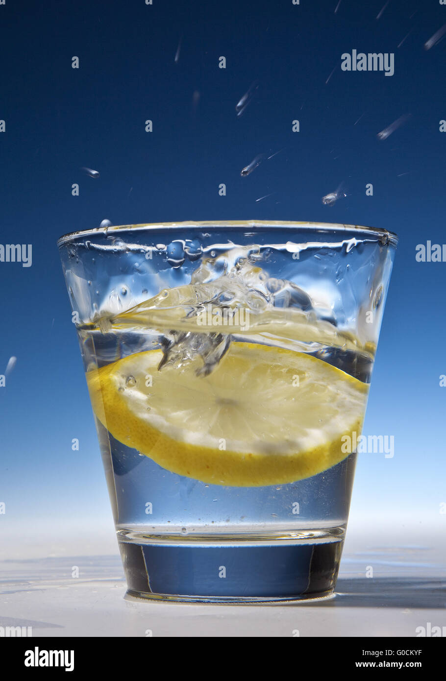 Slice of lemon falling into a glass with water Stock Photo