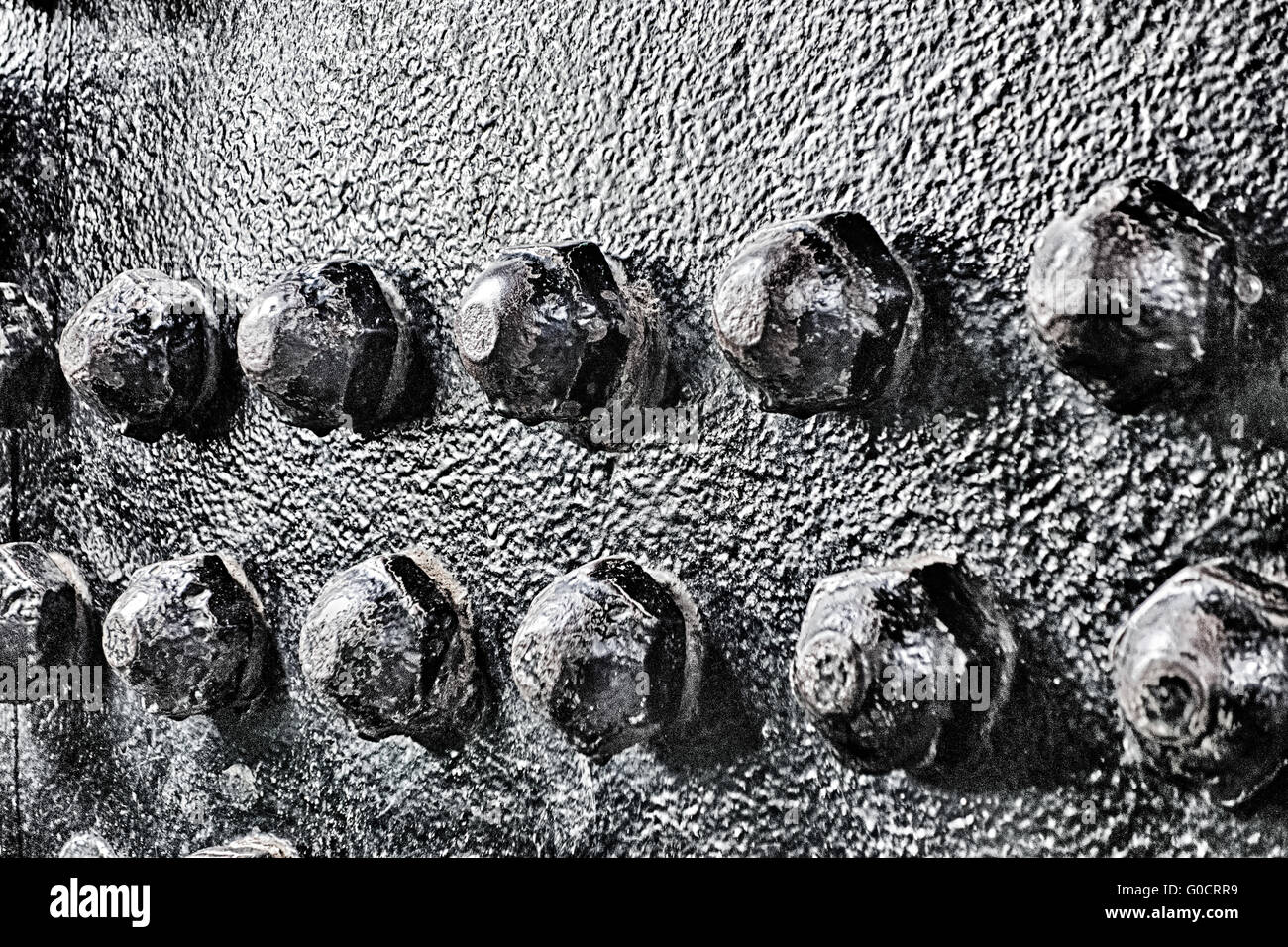 Industrial abstract background texture with black steel structure with bolts and rivets - Stock Image
