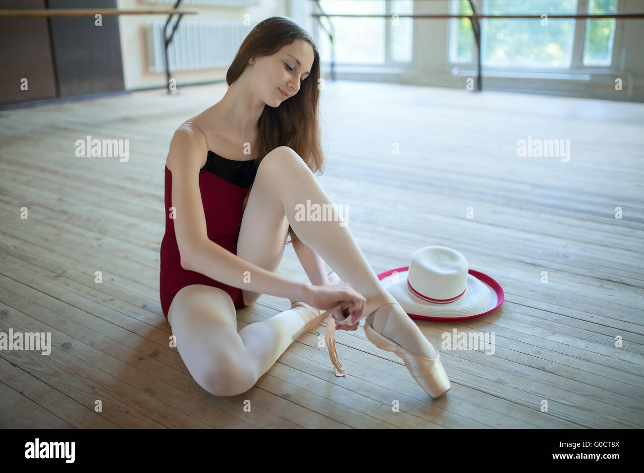 Young ballerina sitting on the floor dance classroom gently tyin - Stock Image
