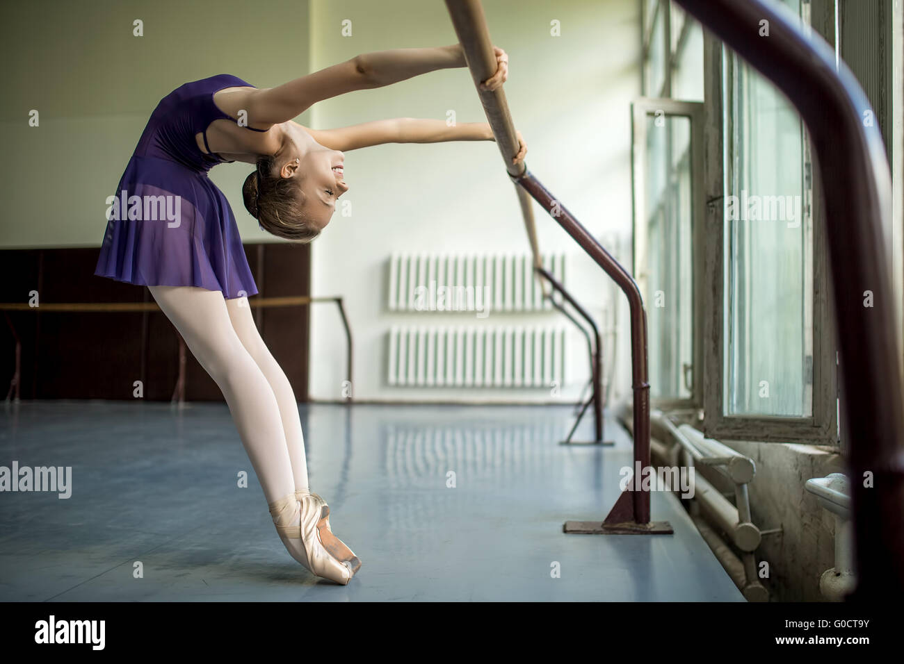 Young dancer doing a workout in the classroom near barre. Stretc - Stock Image