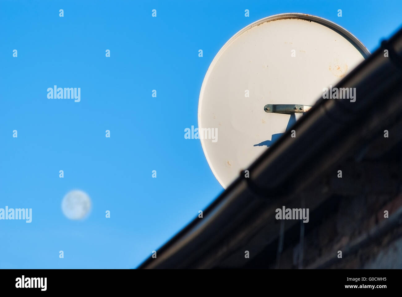 satellite dish on the roof on the background of the moon in the sky - Stock Image
