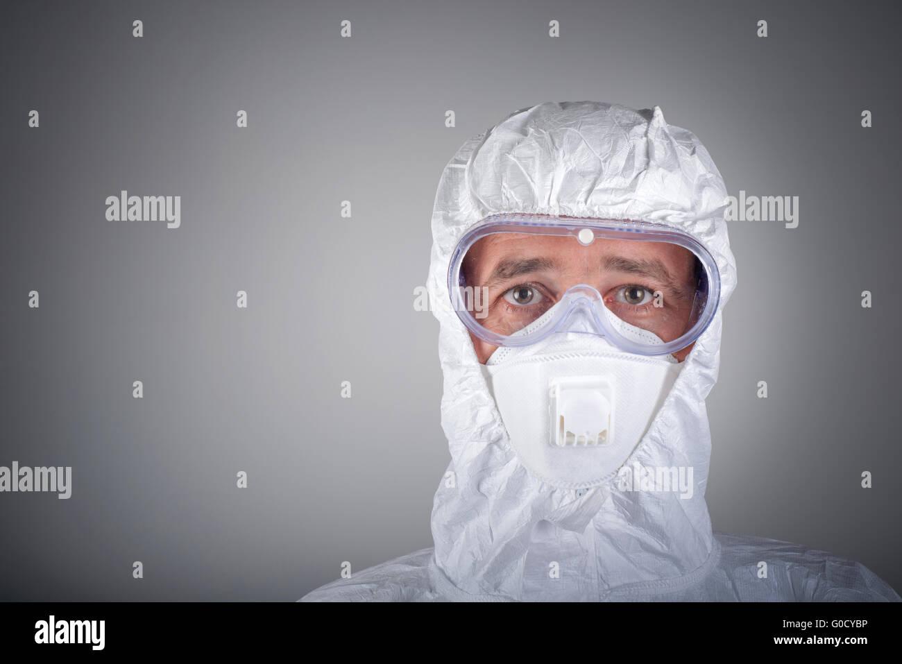 Scientist in protective wear, glasses, respirator - Stock Image
