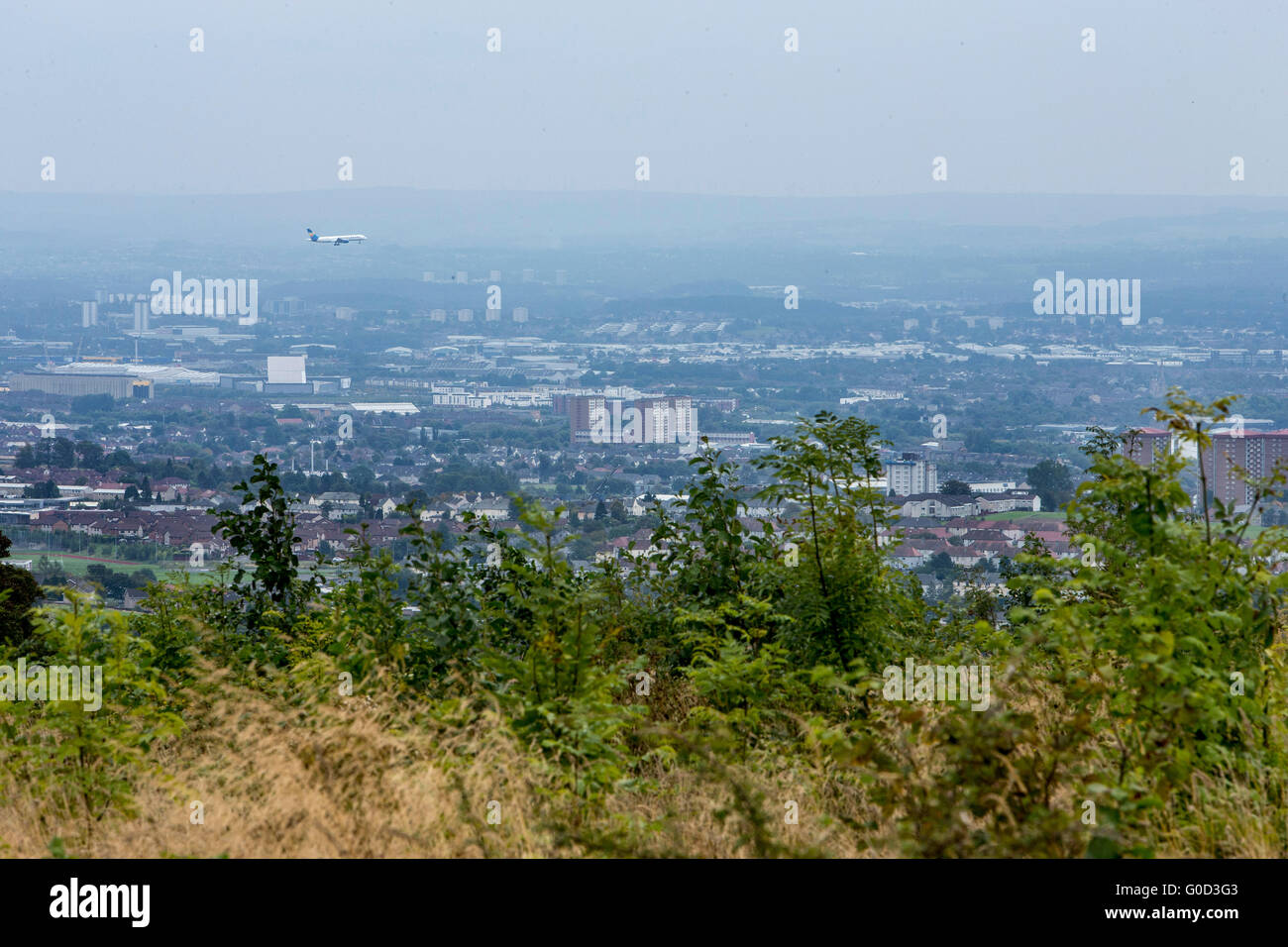Aircraft coming into land at Glasgow Airport with view of Glasgow in background - Stock Image