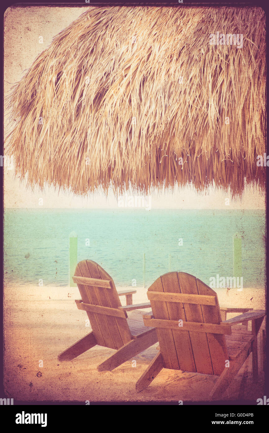 Vacation beach scene with chairs, beach, ocean and hut with vintage retro texture - Stock Image