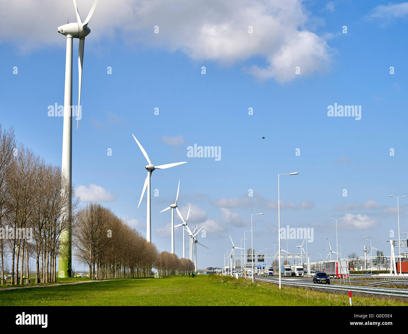 Contrast between sustainable industry and polluting industry. Wind turbine near Europoort, Rotterdam, Netherlands Stock Photo