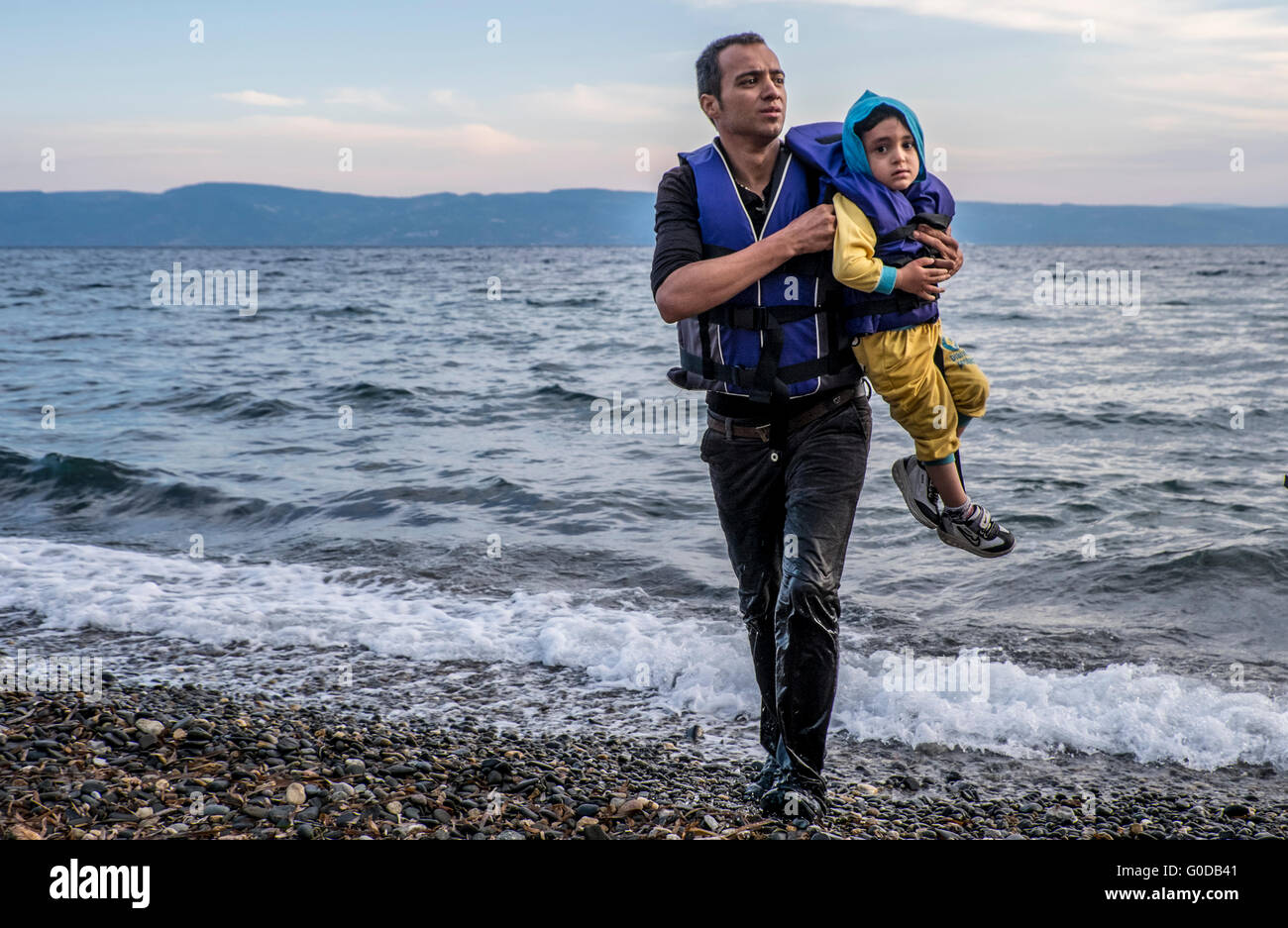 Syrian father and son come ashore on the Greek island of Lesvos after crossing from Turkey in a raft Stock Photo