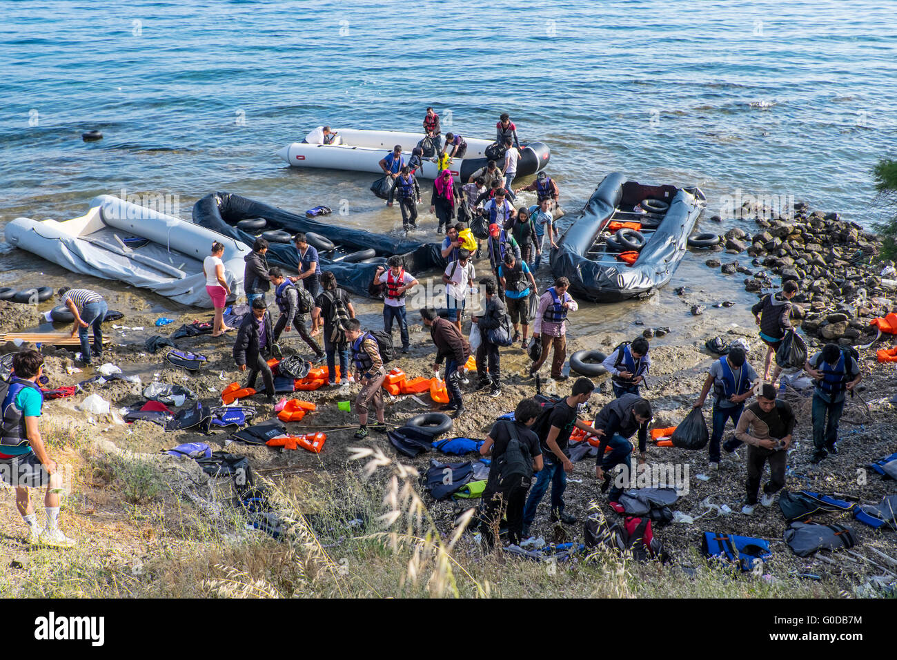 Four rafts of refugees crossing from Turkey to Greece arrive on the northern shore of the Greek island of Lesvos - Stock Image