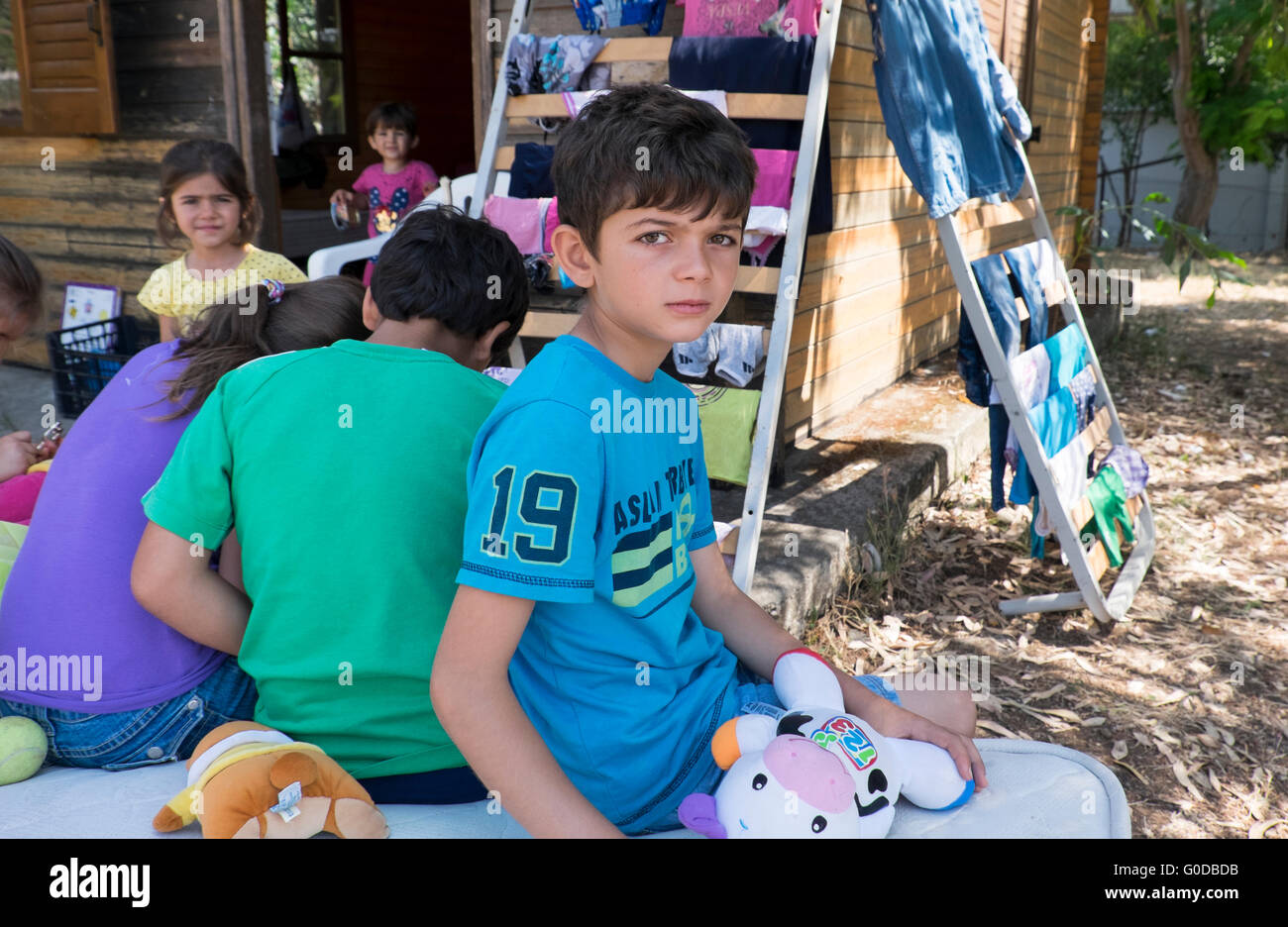 Five Syrian refugee children are given temporary shelter in a camp on the Greek island of Lesvos after crossing Stock Photo