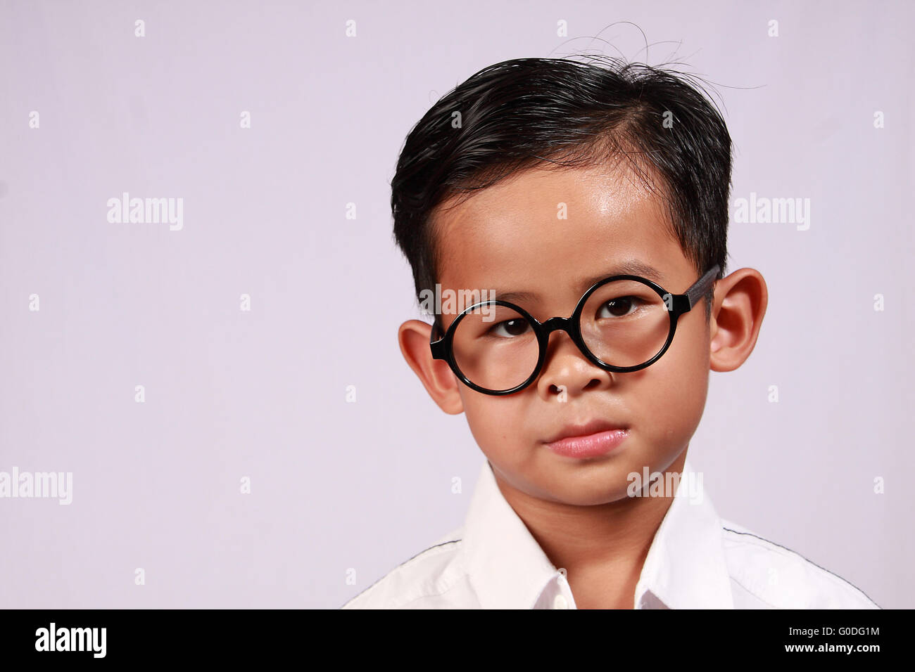 a5fddfa66e1c Portrait of smart young Asian boy with glasses showing his adorable smile -  Stock Image