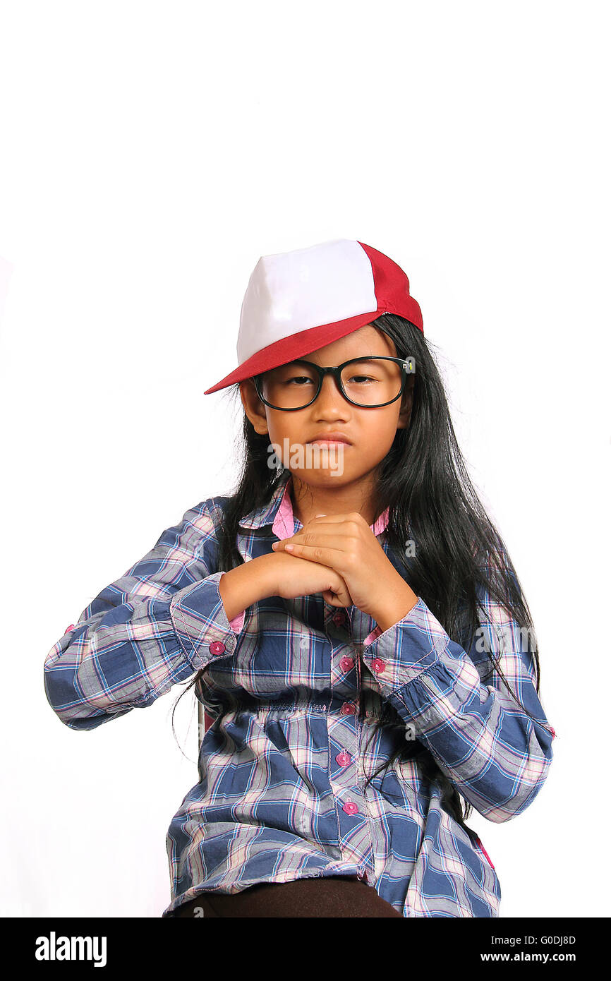 Tough angry little girl with glasses and hat punching her fist into her palm isolated on white - Stock Image