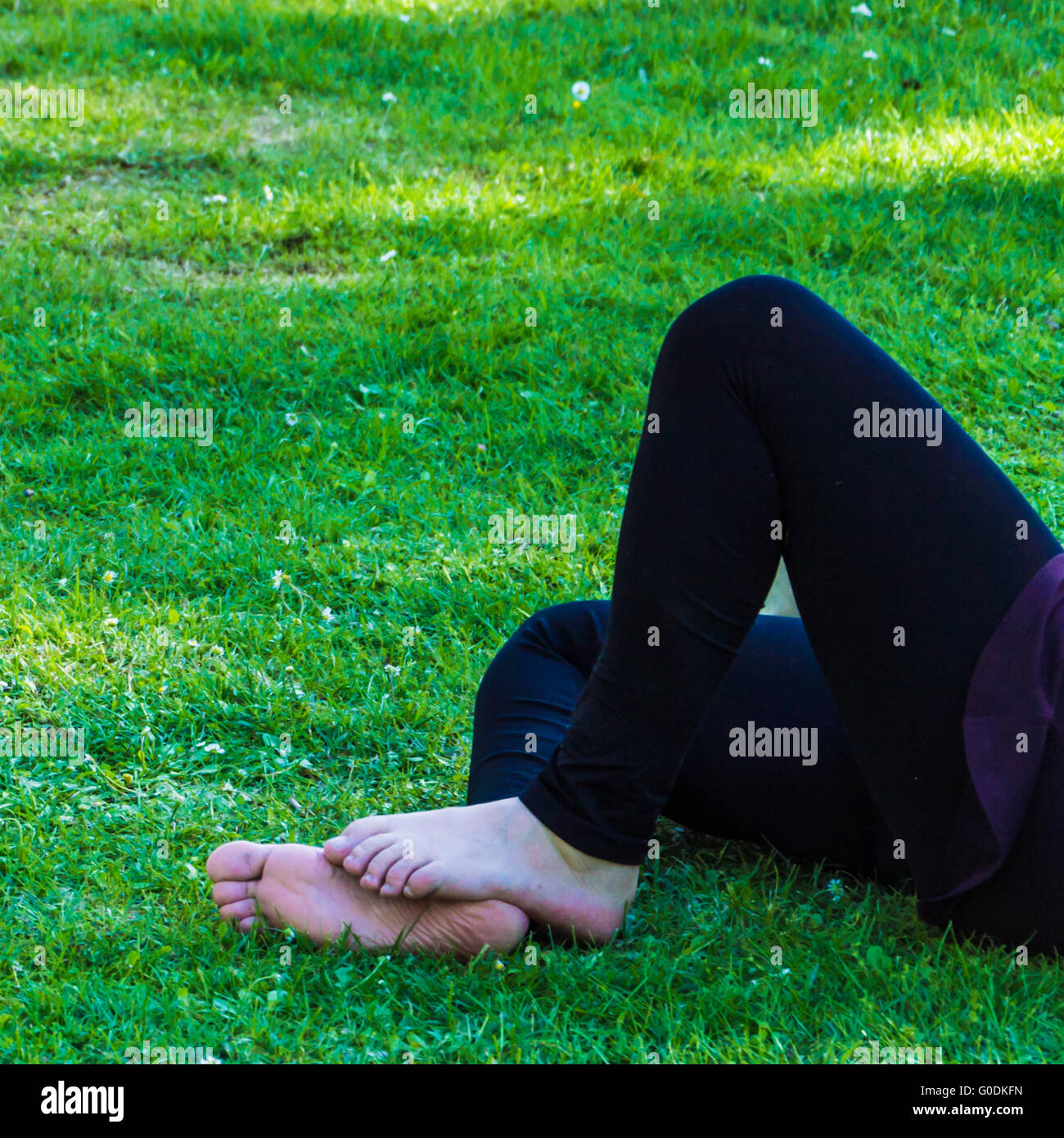 Relaxed feet on green grass - Stock Image