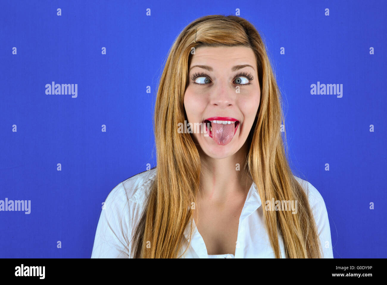 Woman in front of a blue background - Stock Image