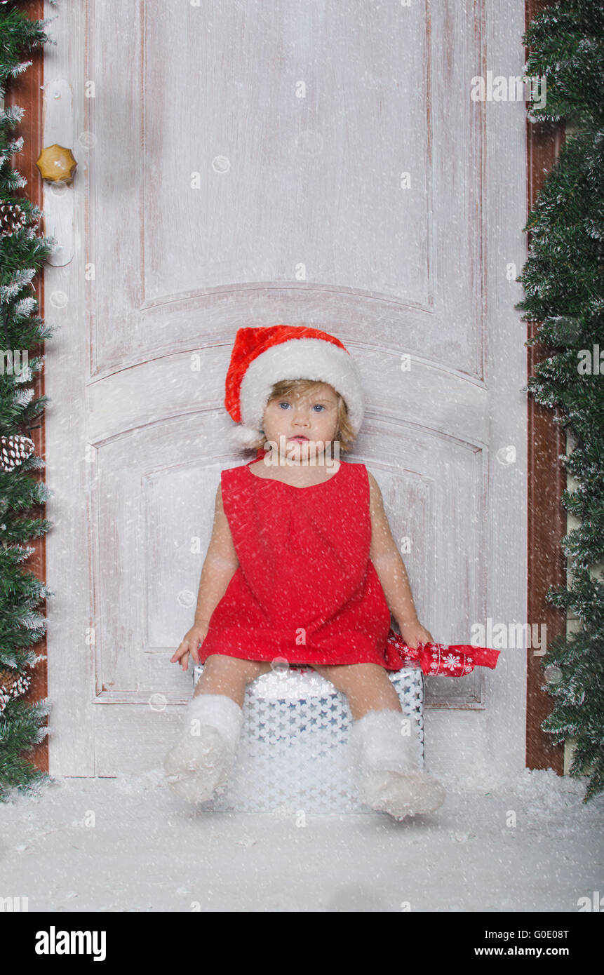 Girl in hat of Santa sitting on box with gifts - Stock Image