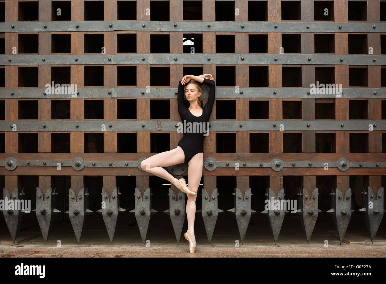 Slim dancer stands on one leg near the old gate - Stock Image