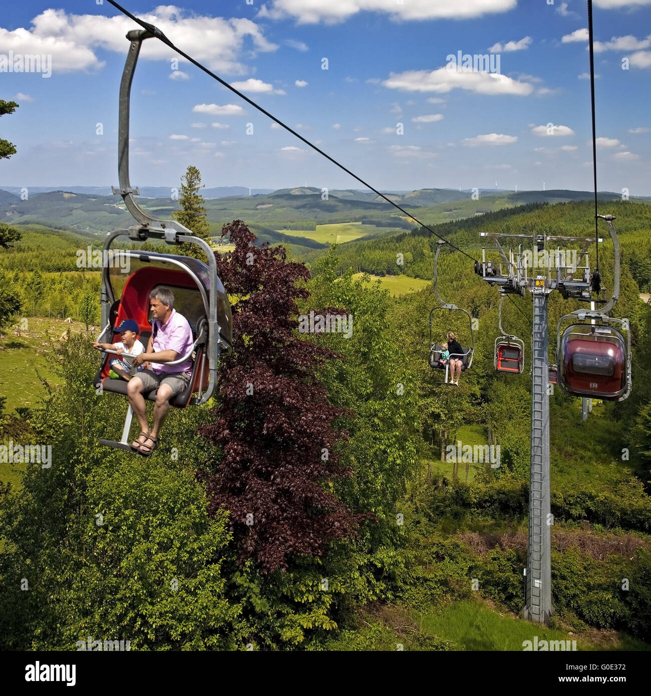 parents with children in a chair lift, Kirchhundem - Stock Image