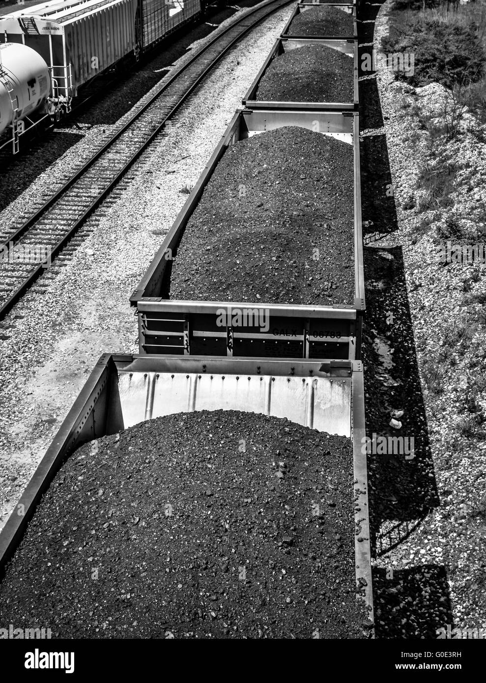 Overhead view of train cars piled high with black coal on railroad tracks along side tanker cars - Stock Image