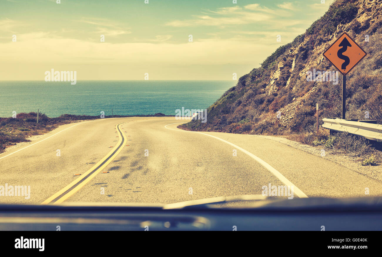Old film stylized road seen through windshield of a moving car, Pacific Coast Highway or State Route 1, California, - Stock Image
