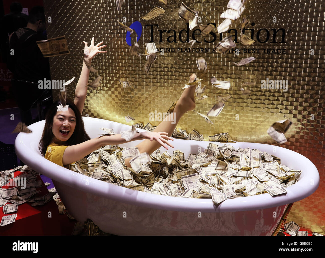 """Chiba, Japan. 30th Apr, 2016. A model scatters toy banknotes in a bath to enjoy feelong of billionaires at a booth of online security company Monex during the Niconico Chokaigi in Chiba on Saturday, April 30, 2016. Some 150,000 visitors enjoyed over 100 booths including games, hobbies, sports, politics as well as Japan's sub cultures at the two-day offline meeting sponsored by Japan's video sharing website """"Niconico Douga"""". © Yoshio Tsunoda/AFLO/Alamy Live News Stock Photo"""