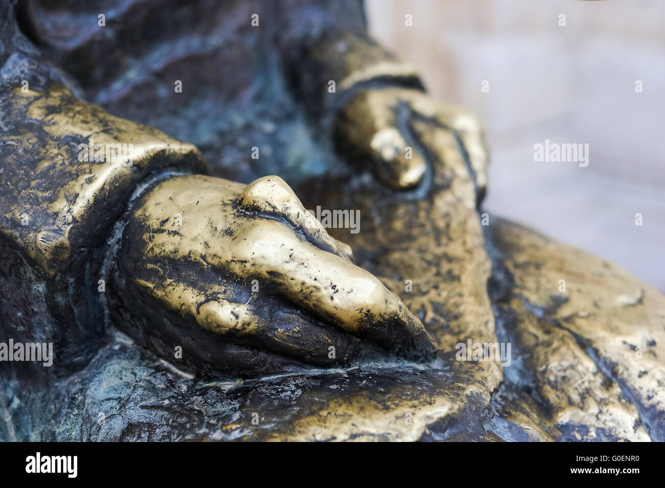Hands of the writer of a bronze statue - Stock Image
