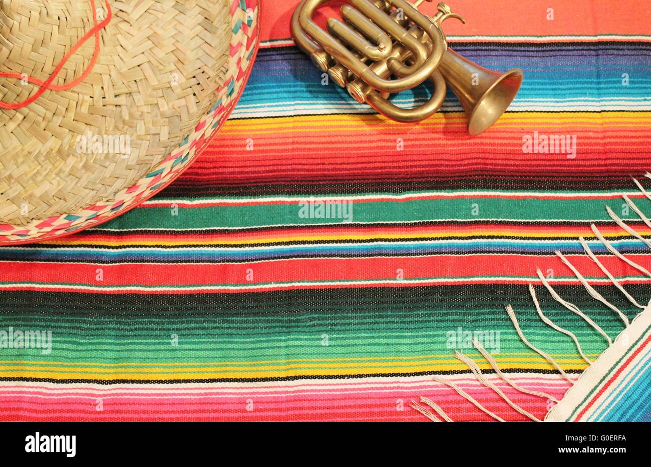 poncho rug  in bright colors with sombrero trumpet - Stock Image