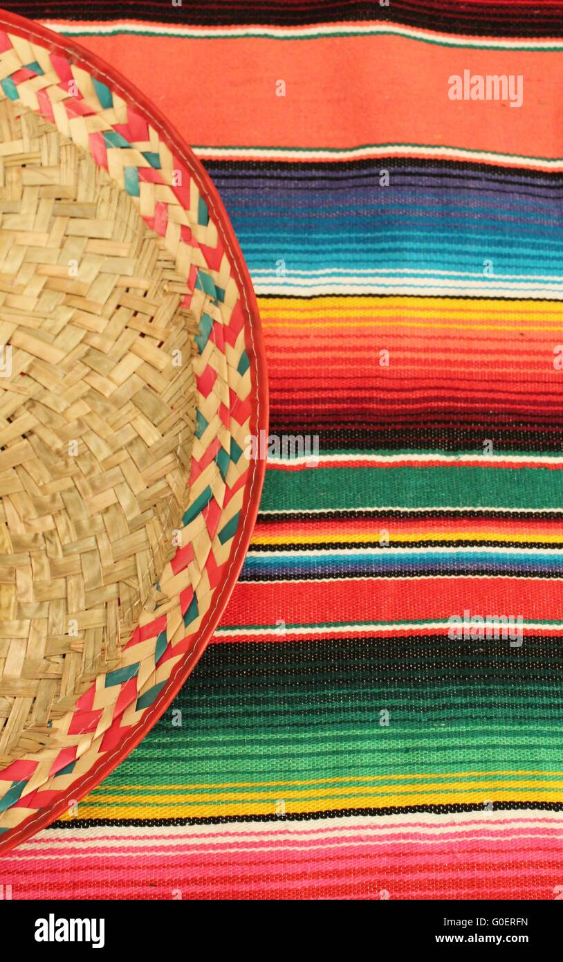 Traditional Mexican fiesta poncho rug  in bright colors with sombrero background with copy space - Stock Image