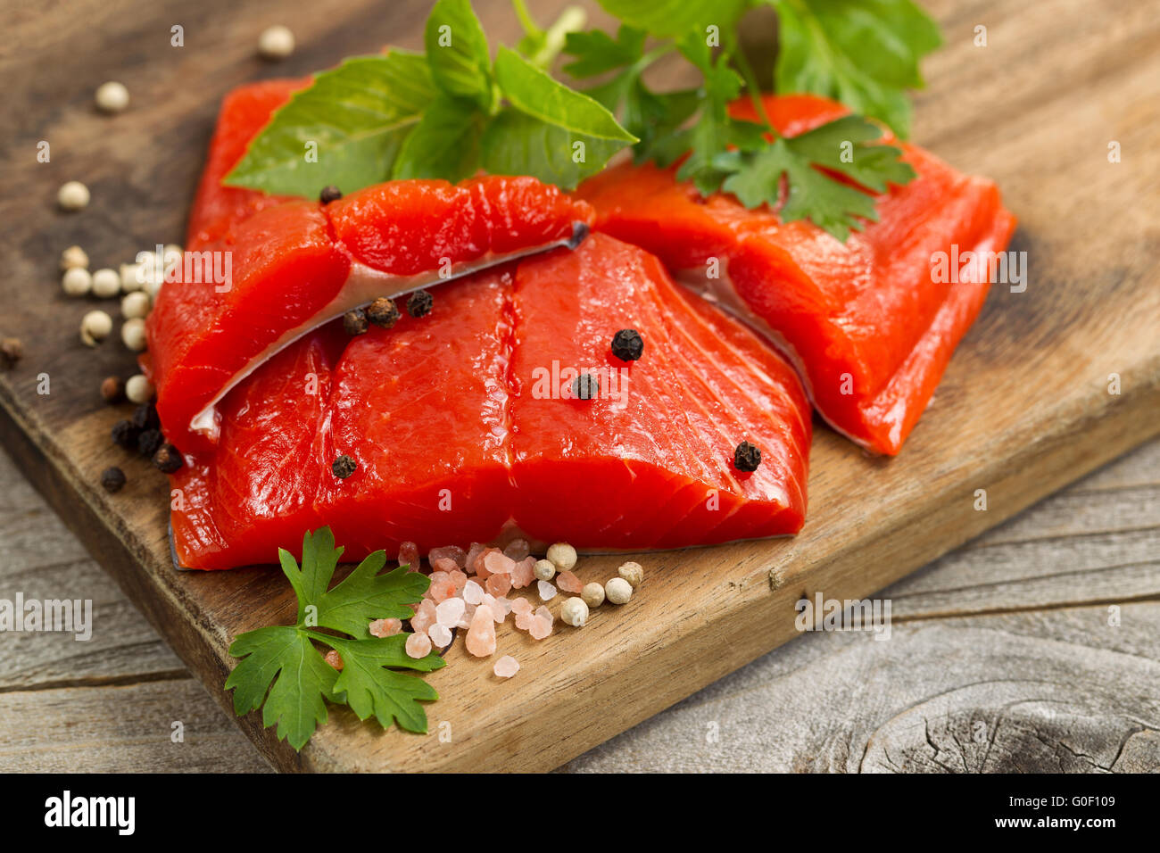 Fresh bright red Copper River Salmon fillets on rustic wooden server with spices and herbs Stock Photo