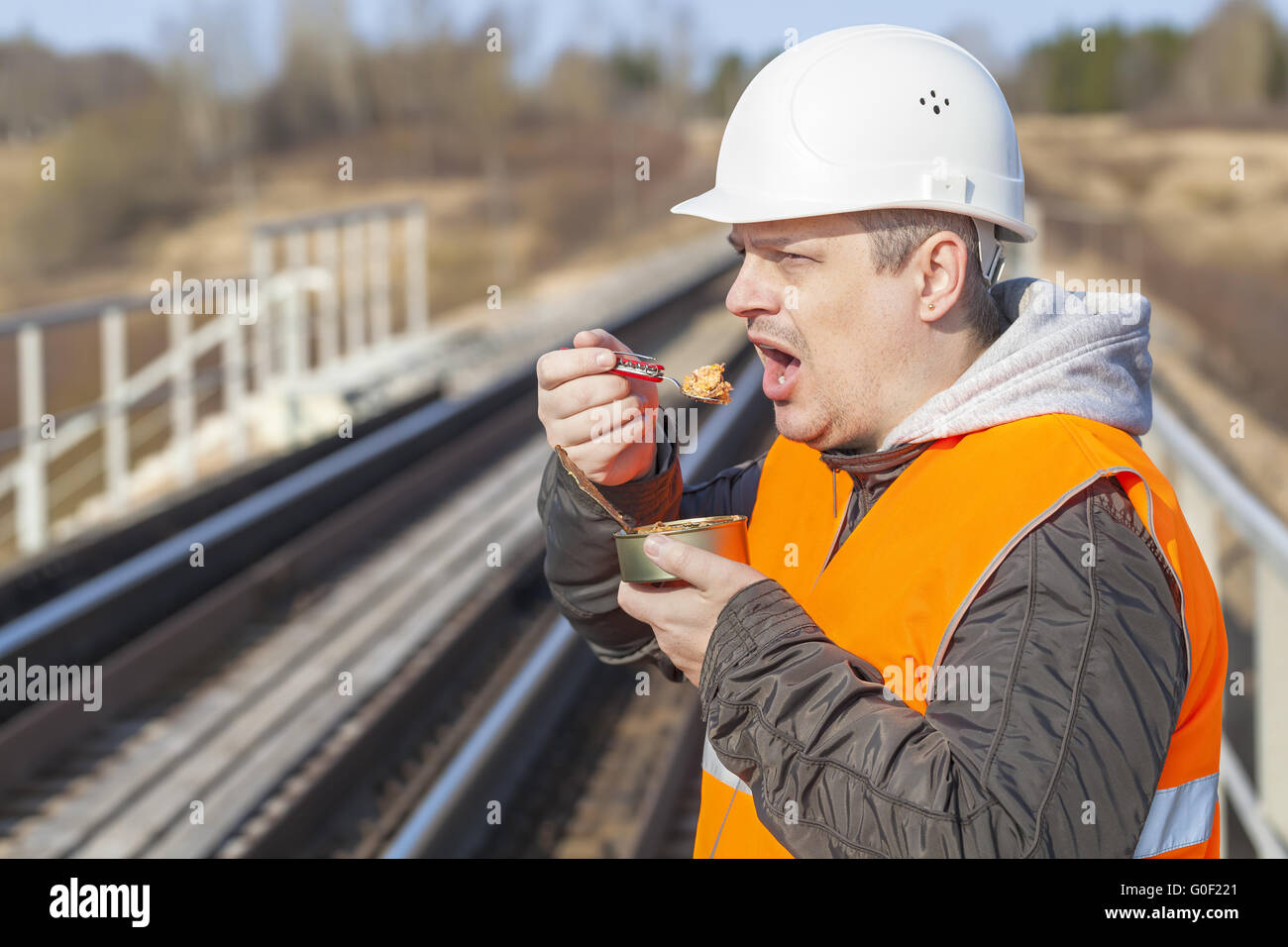 Worker with canned meat on a railway - Stock Image