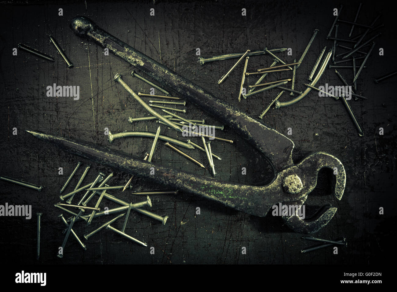 Grunge background with pliers and nails. - Stock Image