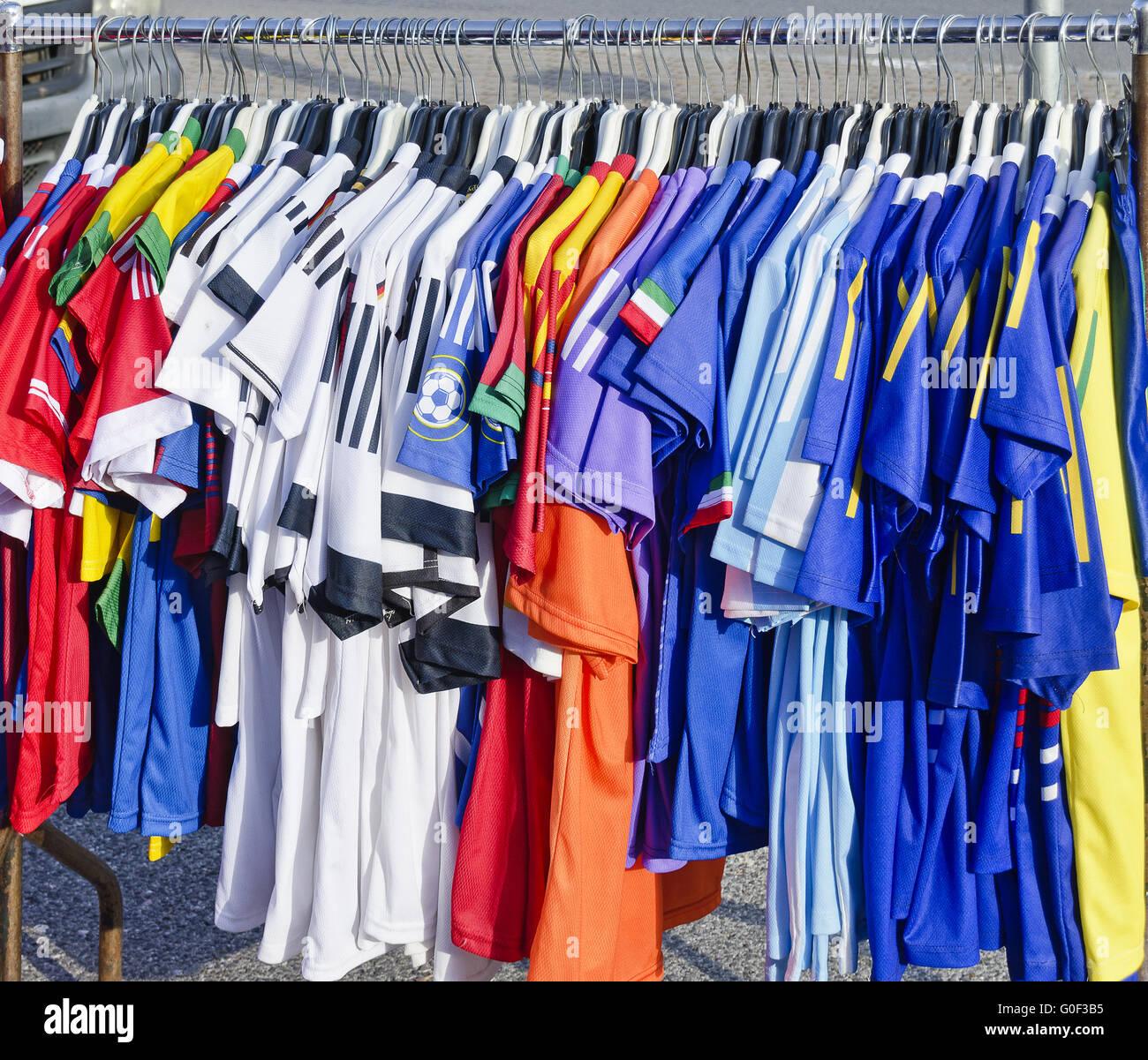 football shirts at a hanging rail - Stock Image