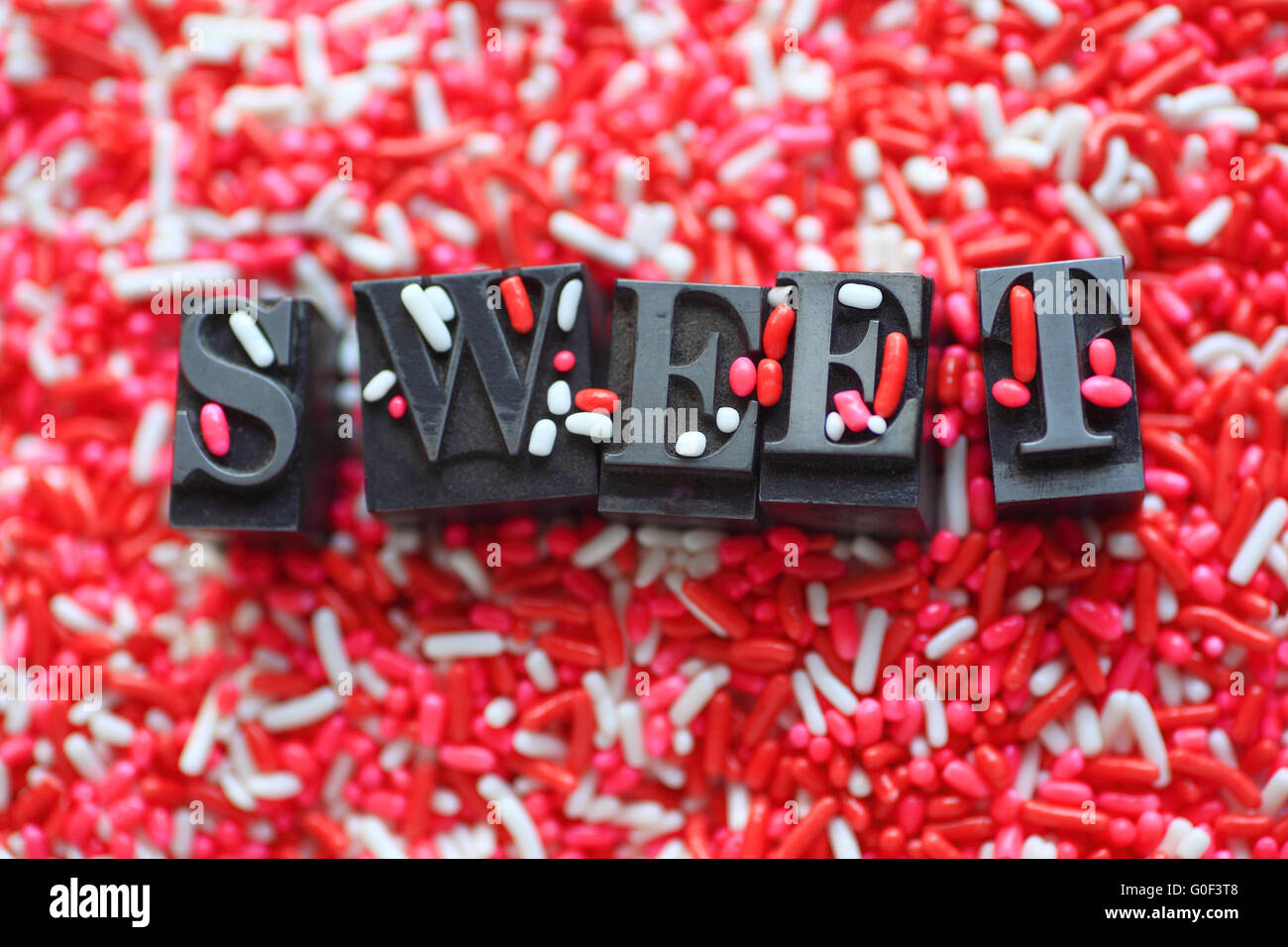 The word 'sweet' in metal type on a pink and white candy sprinkles background - Stock Image