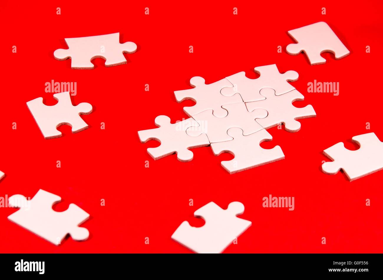 still life with a white jigsaw/puzzle incomplete over a red background, symbol of problem solving - Stock Image