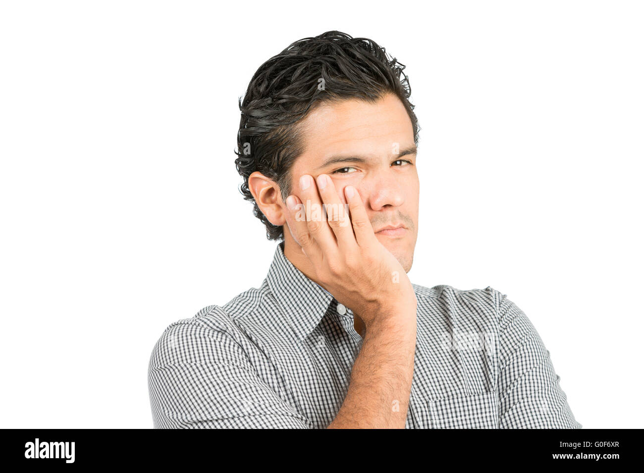 Concerned Hispanic Male Cupping Face Hand At - Stock Image