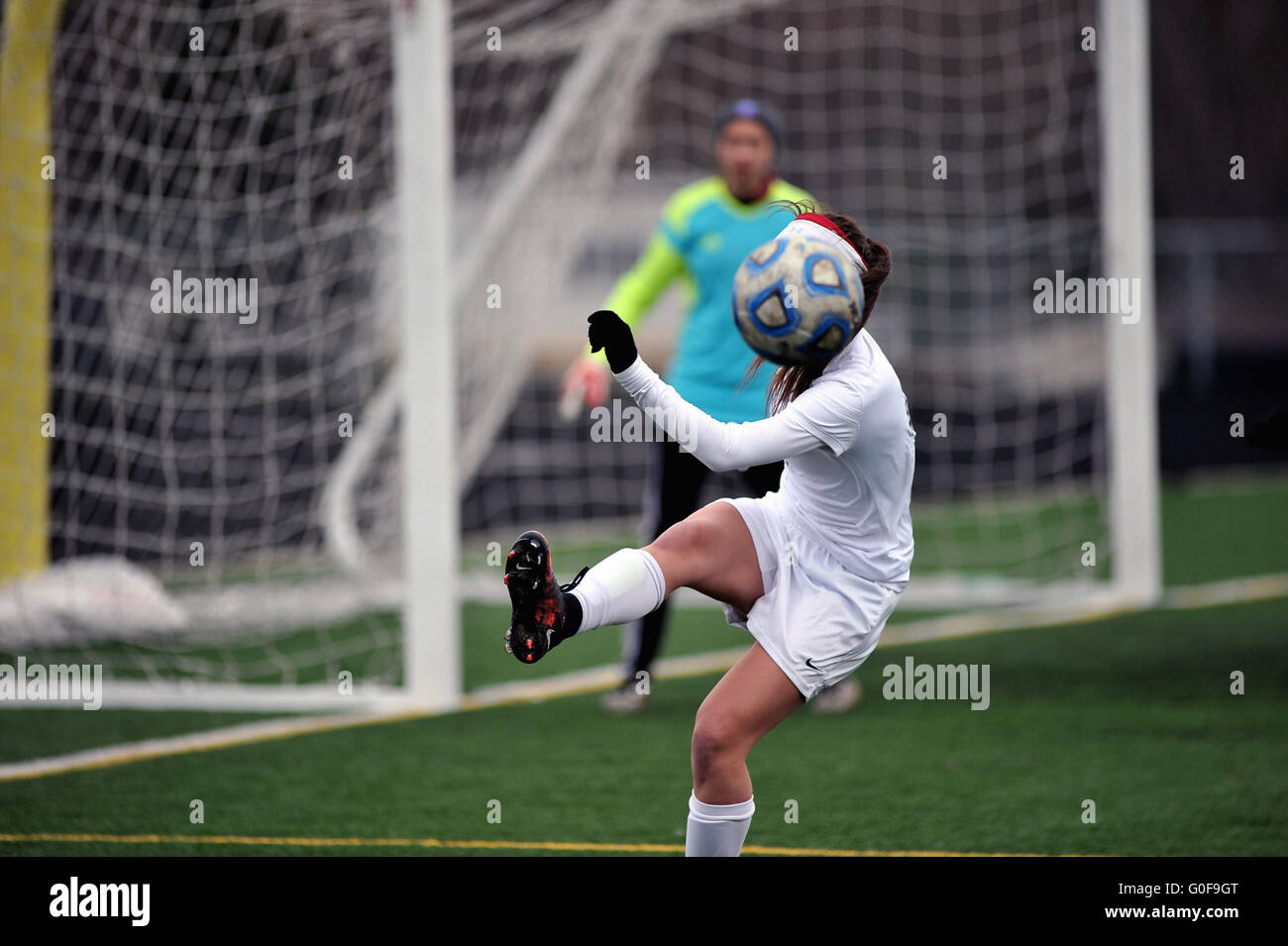 While clearing the ball out of harm's way near her own goal a player's identity is briefly obscured by her - Stock Image