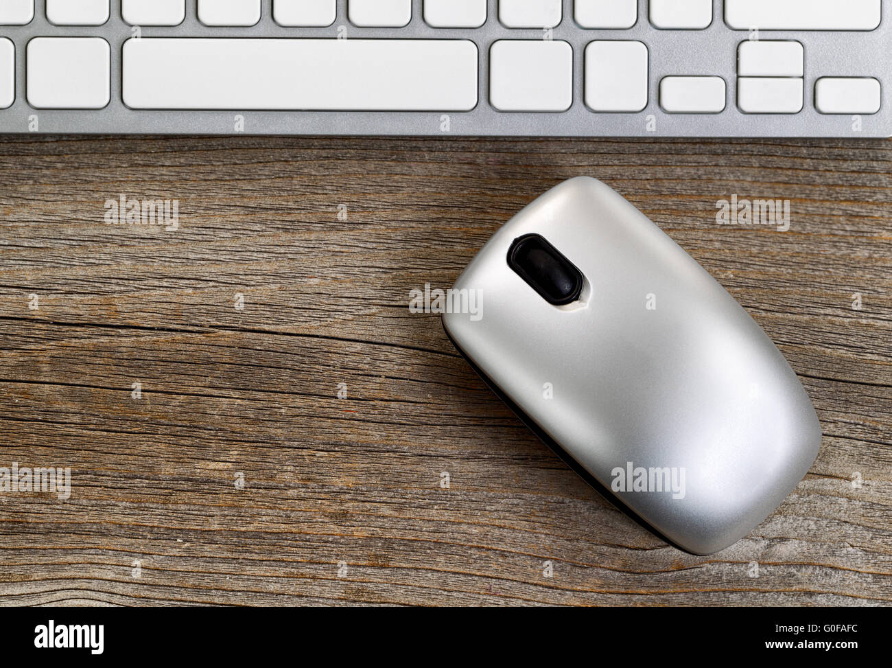 Wireless portable computer mouse with keyboard on rustic wooden desktop - Stock Image