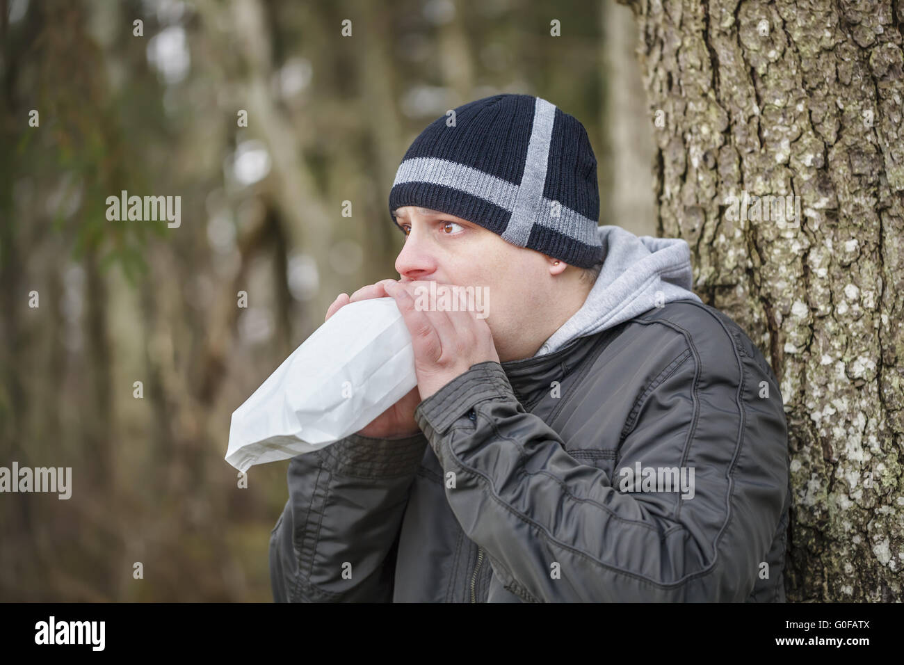 Worried man breathe into a paper bag near tree - Stock Image