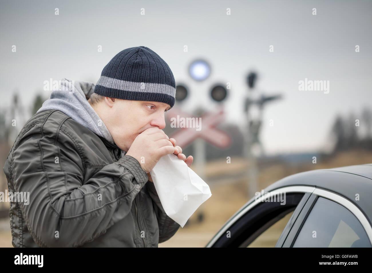 Worried man breathe into a paper bag near rail cro - Stock Image