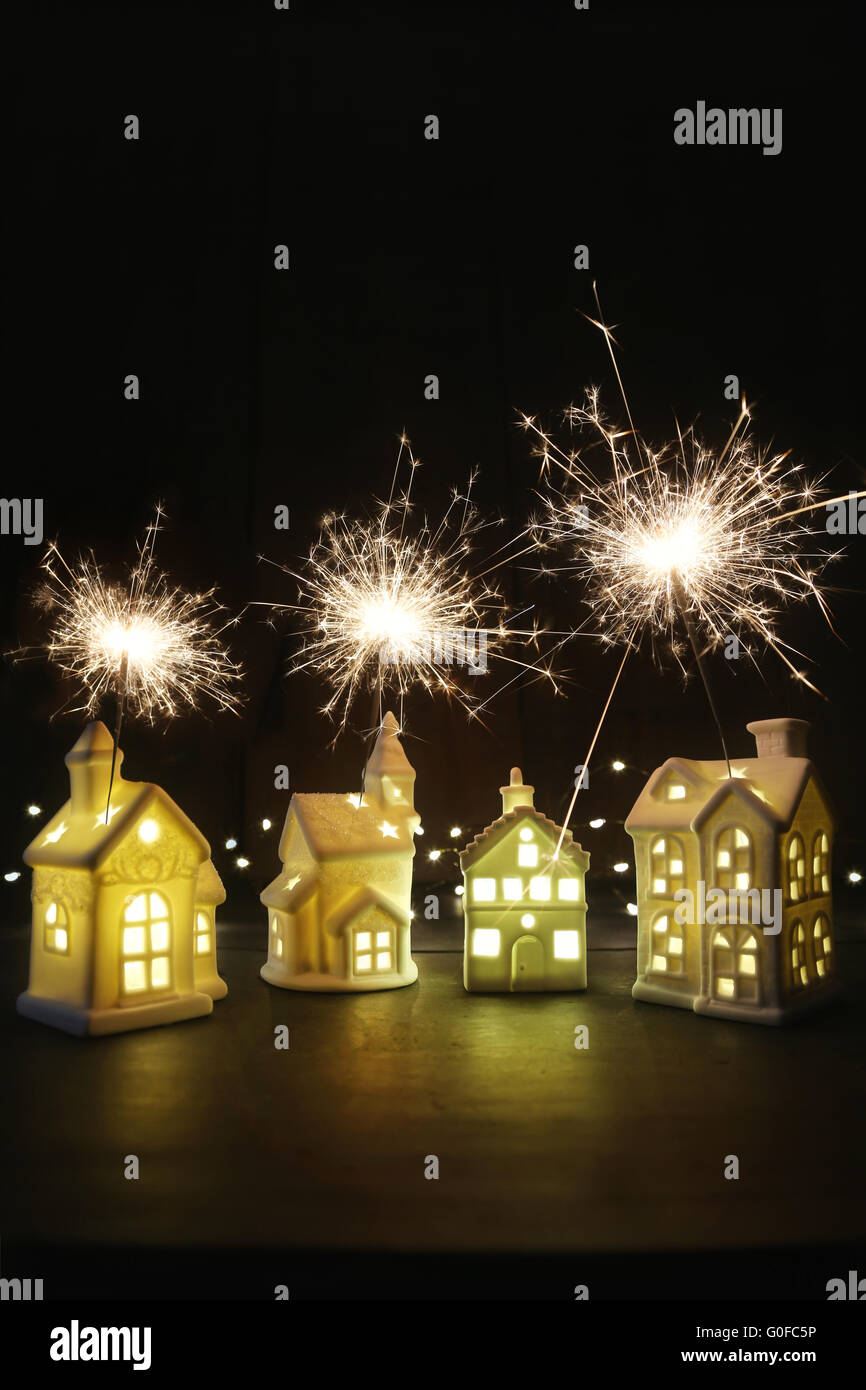 Small ceramic houses with lights and sparklers - Stock Image