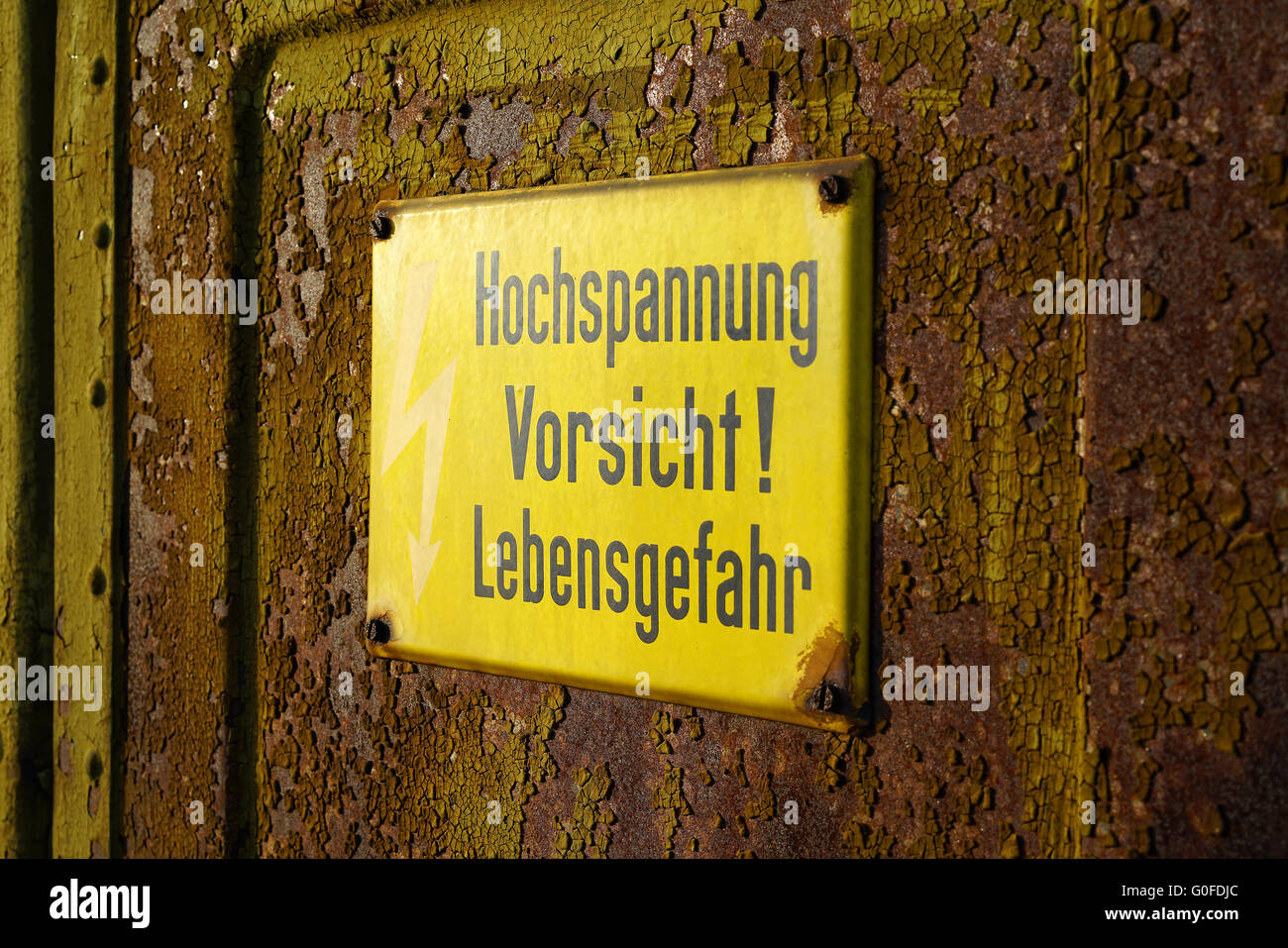 yellow warning sign that says high voltage Caution mortal danger Stock Photo