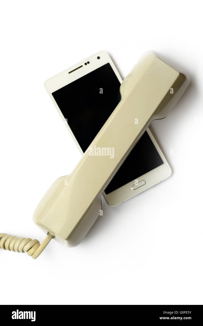 Mobile phone covered by landline handset Stock Photo