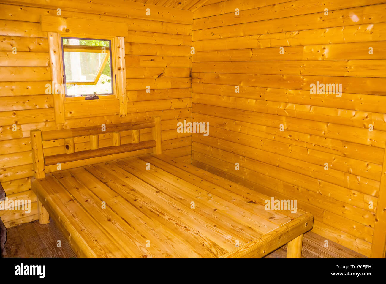 small log cabin interior with bed and window - Stock Image