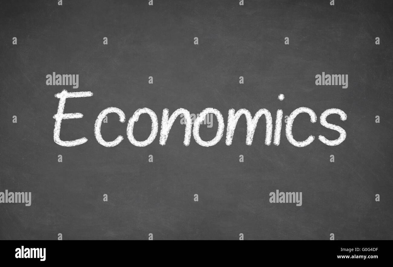 Economics lesson on blackboard or chalkboard. - Stock Image