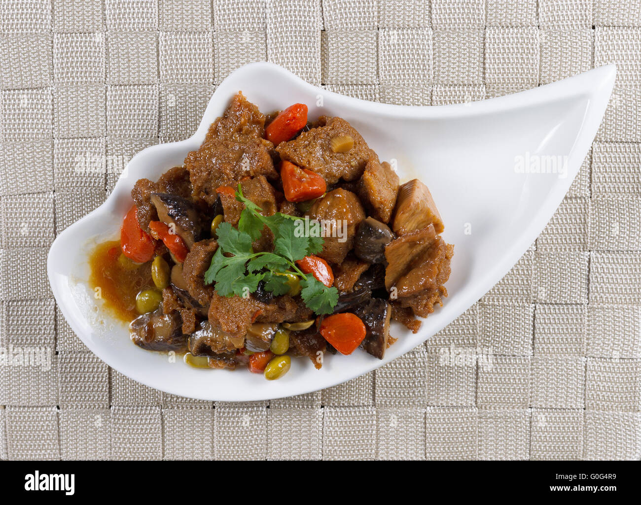 Tofu and vegetables with sauce in small bowl ready to eat - Stock Image