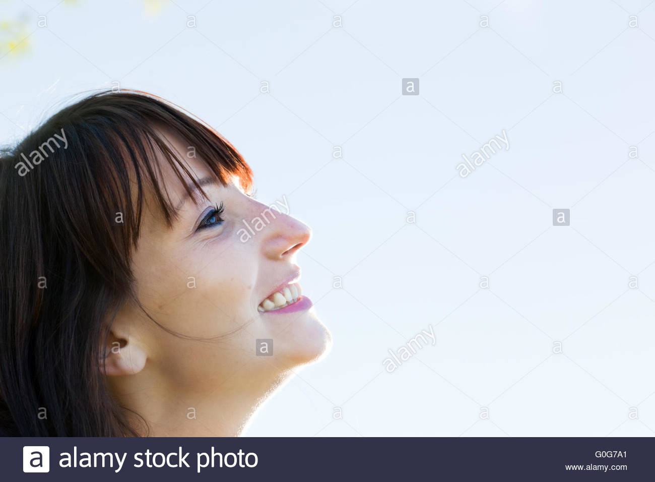 Young pretty woman looking at the sunny sky and smiling. Natural happiness and fun. - Stock Image