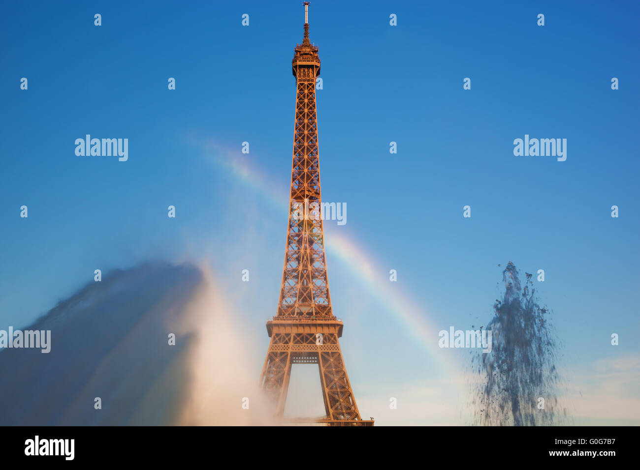 Eiffel Tower seen from fountain making natural rainbow at Jardins du Trocadero at a sunny summer day - Stock Image