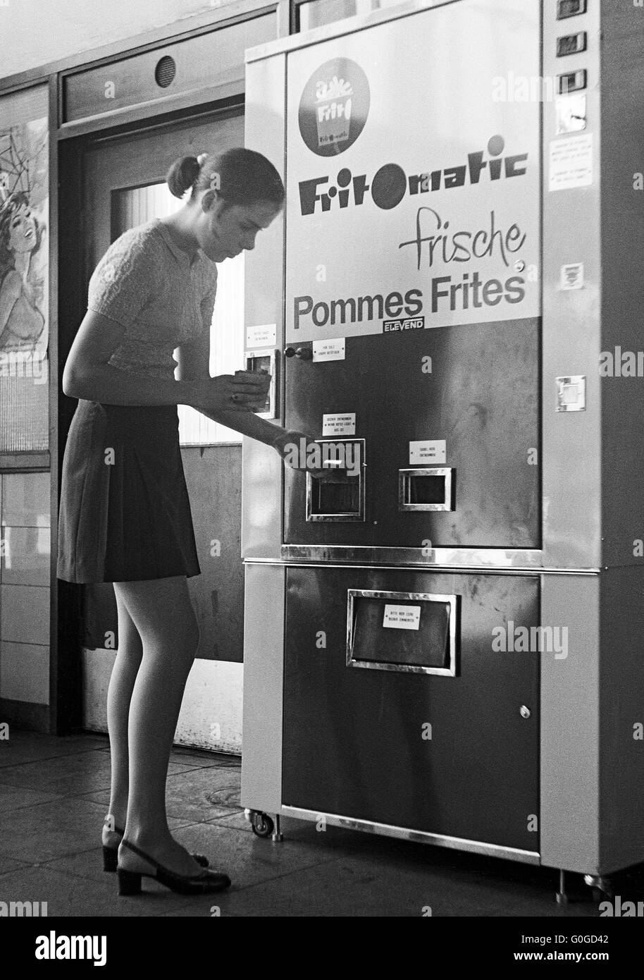 Sixties, black and white photo, people, young girl 14 to 16 years in miniskirt at an automate preparing french-fried - Stock Image