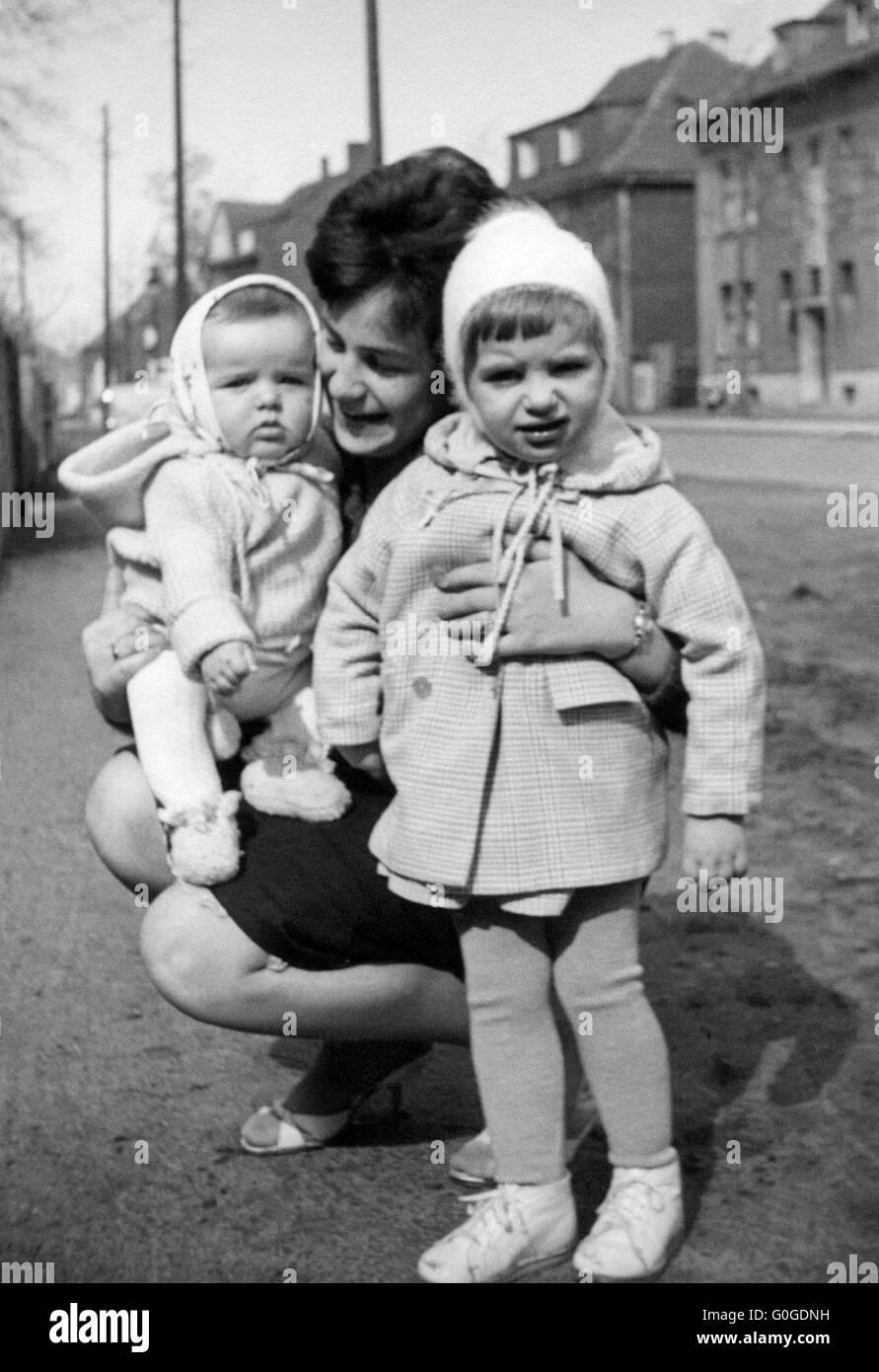 Sixties, black and white photo, people, young woman 20 to 25 years cowers holding a boy 1 year and a girl 2 to 3 - Stock Image